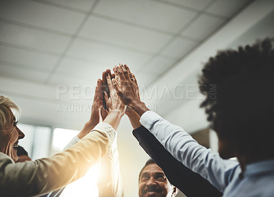 Buy stock photo Cropped shot of a group of colleagues giving each other a high five in an office