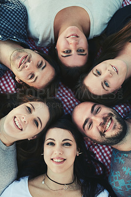 Buy stock photo Portrait of a group of friends lying down with their heads together outdoors