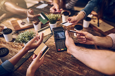 Buy stock photo High angle shot of a group of friends offering their bank cards to pay the bill at a cafe