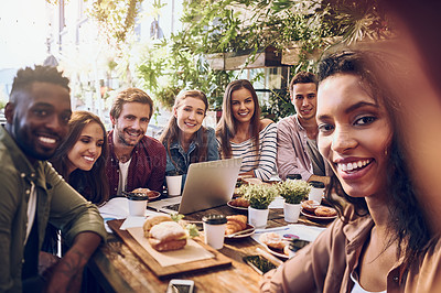 Buy stock photo Shot of a woman taking a selfie with her colleagues while out for lunch