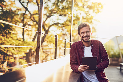 Buy stock photo Cropped shot of a handsome man using his digital tablet outside