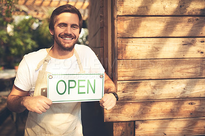 Buy stock photo Cropped shot of an unrecognizable business owner holding up a sign in the doorway of his coffee shop