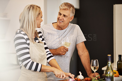 Buy stock photo Shot of a happy mature couple keeping each other company in the kitchen