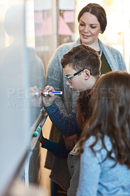 Buy stock photo Cropped shot of an elementary school boy writing on a whiteboard in the classroom