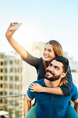 Buy stock photo Shot of a young couple taking a selfie outside