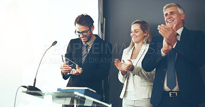 Buy stock photo Cropped shot of two corporate businesspeople applauding the recipient of an award during a ceremony