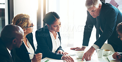 Buy stock photo Cropped shot of a group of corporate businesspeople looking at paperwork in the boardroom