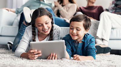 Buy stock photo Shot of a brother and sister using a digital tablet together with their family sitting in the background