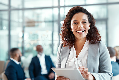 Buy stock photo Portrait of a young businesswoman using a digital tablet in a modern office with her colleagues in the background