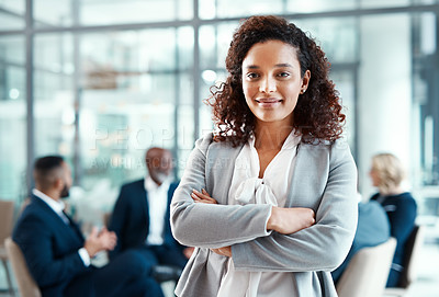 Buy stock photo Portrait of a confident young businesswoman standing in a modern office with her colleagues in the background
