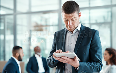 Buy stock photo Shot of a mature businessman using a digital tablet in a modern office with his colleagues in the background