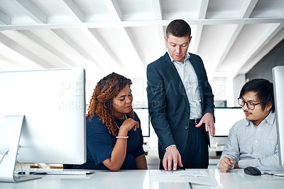 Buy stock photo Shot of three colleagues discussing paperwork at a desk in a modern office
