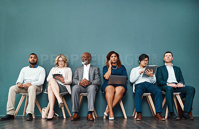 Buy stock photo Studio shot of a group of a diverse group of businesspeople using wireless devices while waiting in line