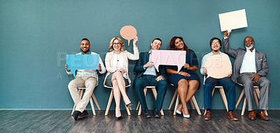 Buy stock photo Shot portrait of a diverse group of businesspeople holding up speech bubbles while they wait in line