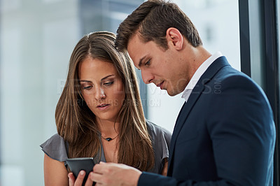 Buy stock photo Cropped shot of two businesspeople looking at something on a cellphone