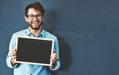 Buy stock photo Studio portrait of a young man holding a blackboard against a grey background