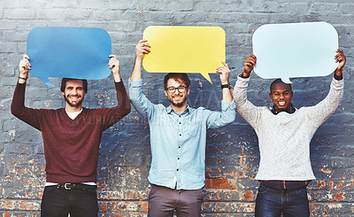 Buy stock photo Portrait of a group of young men holding speech bubbles against a brick wall
