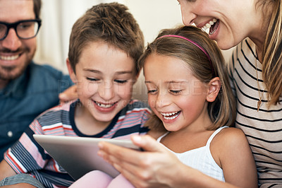 Buy stock photo Shot of an adorable brother and sister using a digital tablet together with their parents on the sofa at home