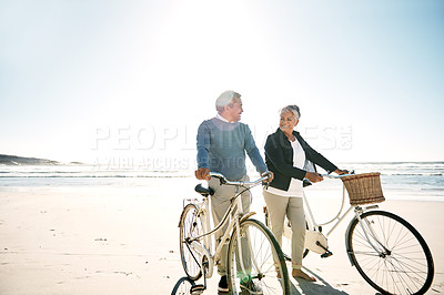 Buy stock photo Shot of a senior couple walking alongside their bikes on the beach