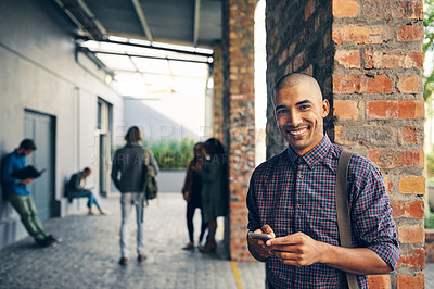 Buy stock photo Portrait of a young man using a mobile phone outdoors on campus