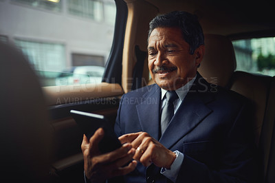 Buy stock photo Shot of a mature businessman using a phone and digital while traveling in a car