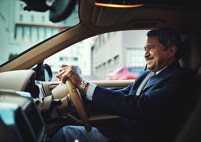 Buy stock photo Shot of a mature businessman driving a stylish car