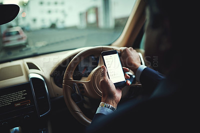 Buy stock photo Cropped shot of a businessman using his phone's gps while driving a car