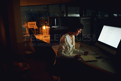 Buy stock photo Shot of a young businesswoman writing in a notebook during a late night at work