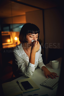 Buy stock photo Shot of a young businesswoman blowing her nose during a late night at work
