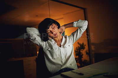 Buy stock photo Shot of a young businesswoman experiencing strain during a late night at work