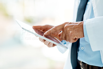 Buy stock photo Cropped shot of a male doctor using his digital tablet