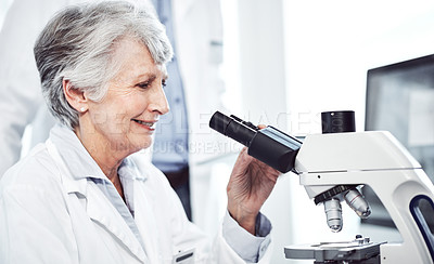 Buy stock photo Shot of a cheerful elderly female  scientist looking through a microscope while being seated in a laboratory