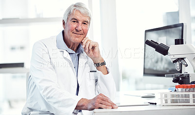 Buy stock photo Portrait of a cheerful elderly male scientist making notes while looking into the camera and being seated inside a laboratory