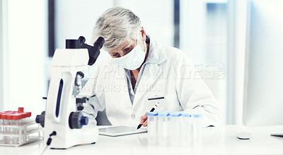 Buy stock photo Shot of a focused elderly female scientist working and making notes while wearing a doctor's mask inside of a laboratory