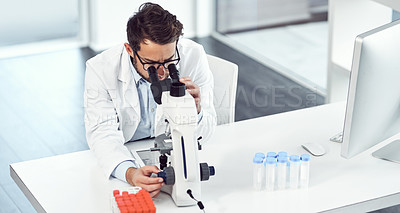 Buy stock photo Shot of a focused young male scientist looking through a microscope inside of a laboratory