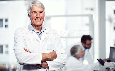 Buy stock photo Portrait of a cheerful elderly male scientist standing with arms folded while looking into the camera inside a laboratory
