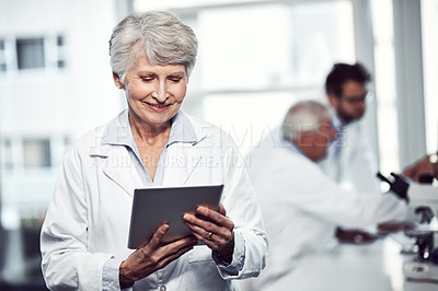 Buy stock photo Shot of a cheerful elderly female scientist using a digital tablet while standing inside of a laboratory
