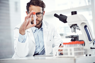 Buy stock photo Shot of a focused young male scientist examining a test tube while being seated inside a laboratory