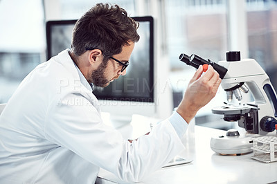 Buy stock photo Shot of a focused young male scientist making notes while holding up a test tube inside of a laboratory