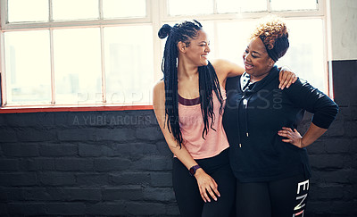 Buy stock photo Shot of two cheerful young women having a conversation before a workout session in a gym