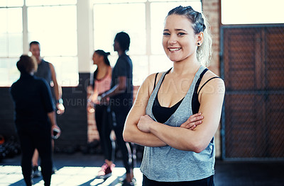 Buy stock photo Portrait of a cheerful young woman standing with her arms folded while looking into the camera before a workout in a gym