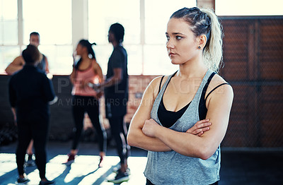 Buy stock photo Shot of a focused young woman standing with arms folded while contemplating before a workout in a gym