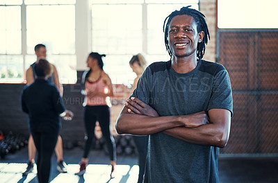 Buy stock photo Portrait of a cheerful young man standing with his arms folded while looking into the camera before a workout in a gym