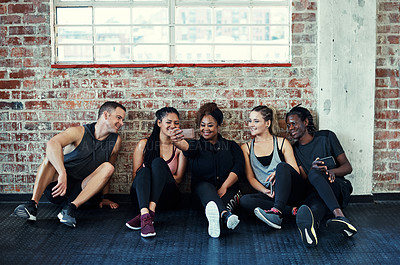 Buy stock photo Shot of a cheerful young group of people sitting down on the floor and taking a self portrait together in a gym