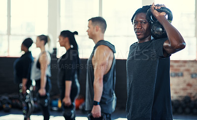 Buy stock photo Shot of a focused group of young people standing in a row and training with weights  while one looks into the camera in a gym