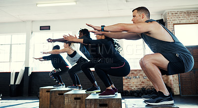 Buy stock photo Shot of a focused group of young people doing lunges on crates as exercise inside of a gym