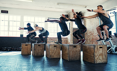 Buy stock photo Shot of a focused group of young people jumping onto crates as exercise inside of a gym