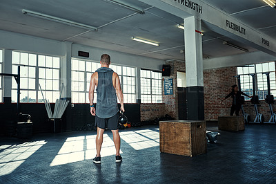 Buy stock photo Rearview shot of an unrecognizable man lifting kettlebells in a gym