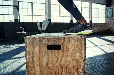 Buy stock photo Shot of an unrecognizable man doing jumping exercises on a wooden block in a gym