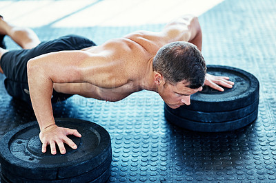 Buy stock photo Shot of a young man doing push ups with weights in a gym